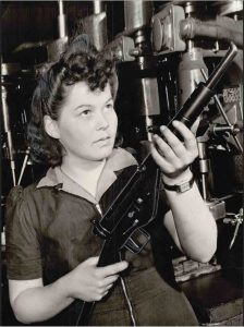 Image of a female factory worker holding a gun.