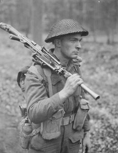 Photograph of a soldier from WW2, carrying a gun through the forest