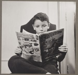 A child at the Children's Colony, a school for refugee children in New York, N.Y. reading a Superman comic.