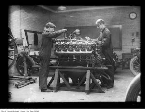 Fig. 4. Unknown. Archived. Captured in black and white, vintage photograph of three boys working on the mechanics of an aviator machine at Wester Technical School.