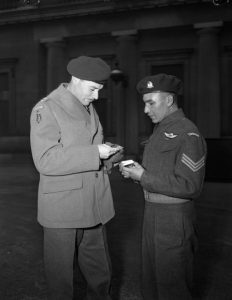 Lieutenant-Colonel J.F.R. Akehurst looks at Sergeant Tommy Prince's Military Medal, black and white.